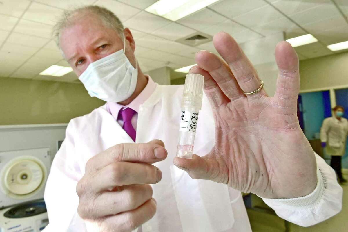 Mark Kidd, Clinical Laboratory and Scientific Director of the Branford based Wren Laboratories, holds a first generation Wren Saliva Collection tube from a Wren Laboratories saliva-based PCR test for COVID-19, in 2020.