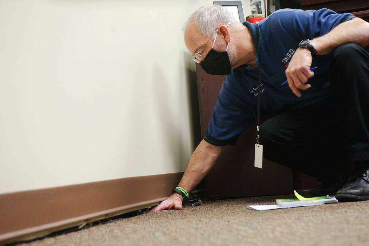Pasadena ISD Maintenance Director Tom Douglas uses his hand to measure the degree of separation between the baseboard and flooring due to foundation problems throughout the Pasadena ISD administration building on Cherrybrook. The district has approved construction of a new building to house its administration.