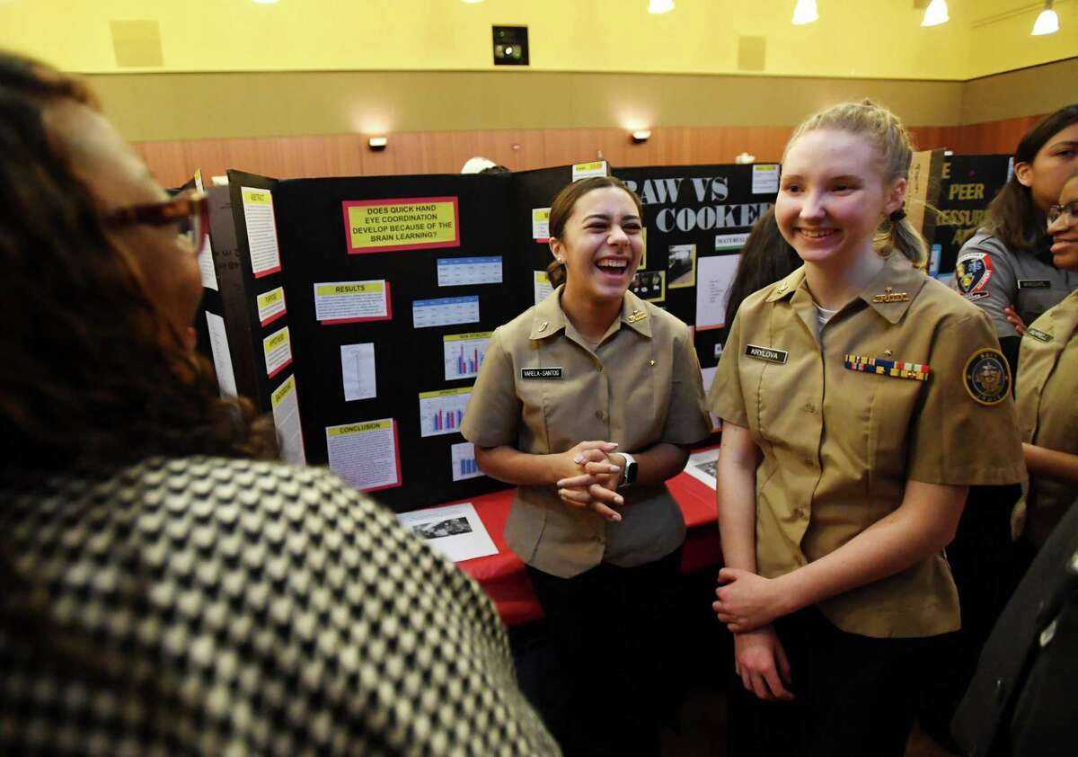Bridgeport Military Academy students Brenda Varela-Santos, 15, center, of Bridgeport, and Valery Krylova, 16, of Shelton, present their project on how hand eye coordination develops to judge Faith Villegas at the annual Bridgeport Science Fair finals at Sacred Heart University in Fairfield, Conn. on Tuesday, February11, 2020.