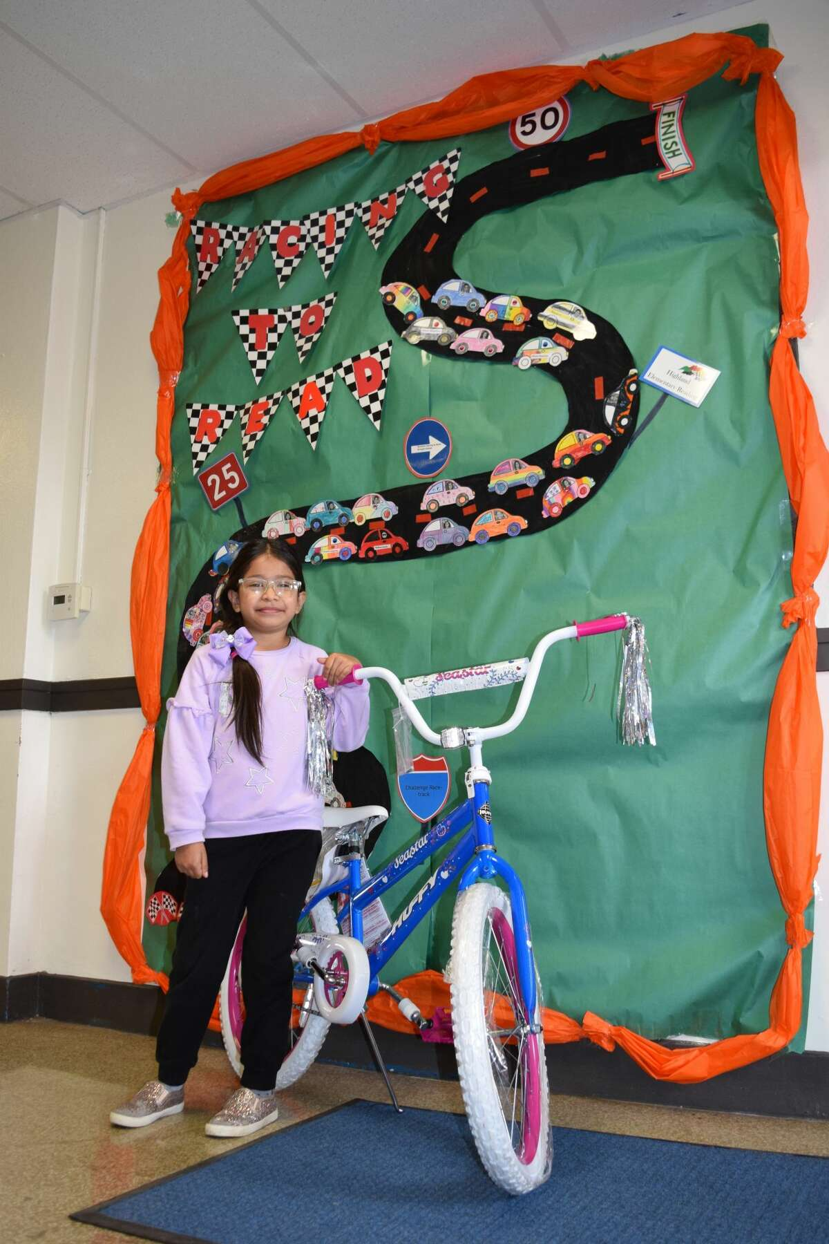 Highland second grader Hailey Cruz stands with the prize bicycle she won in a drawing for reaching her reading challenge goal for the spring semester of the 2020-2021 school year.