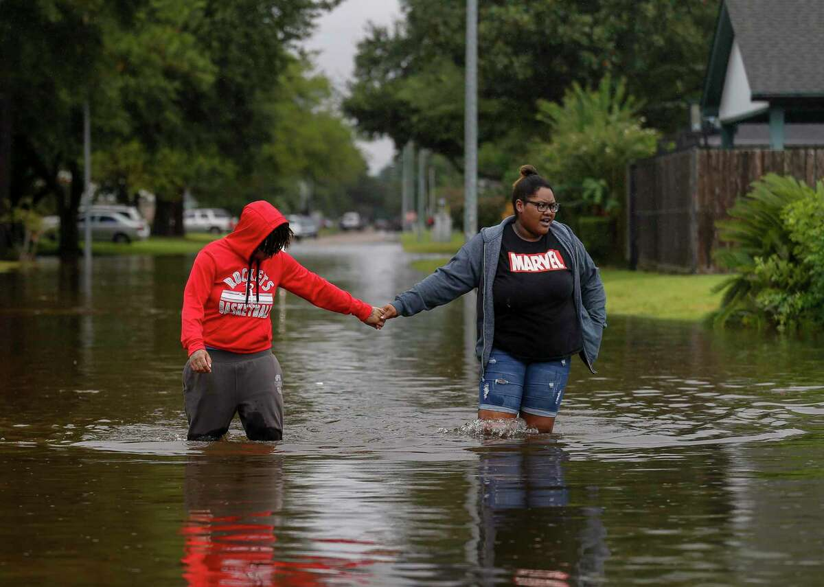 Harris Carraway, left, and her girlfriend Tanelle Wallace make their way through a flooded street to get to the store during Tropical Storm Beta on Tuesday, Sept. 22, 2020, in Houston.