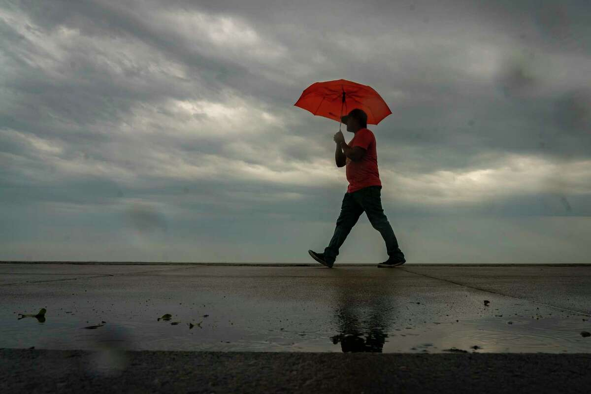Edgar Macias, of Stephenville, walks along the Seawall through the rain, Sunday, March 28, 2021, in Galveston. Macias and his family had been visiting Houston for a church service on Saturday, and they decided to spend Sunday visiting Galveston before driving home.