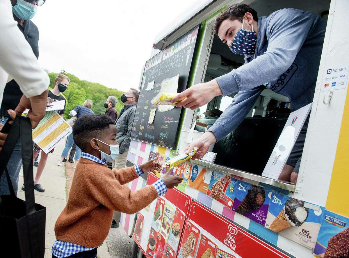 Ari Enu, 5, of Wilton receives ice cream from Jack Lewis of College Creamery at Wilton Library's ice cream social on Saturday, May 8, 2021, in Wilton, Connecticut. New residents were invited to gather and receive individually-wrapped ice cream bars courtesy of the library's Board of Trustees. The social commemorates the library's 125th anniversary.