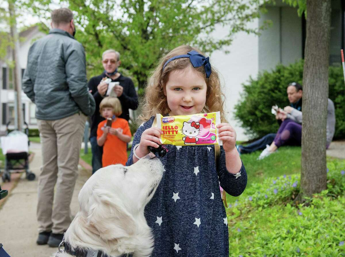 Dakota Kennedy, 4, and her dog, Harlow, of Wilton, receive ice cream from Jack Lewis of College Creamery at Wilton Library's ice cream social on Saturday, May 8, 2021, in Wilton, Connecticut. New residents were invited to gather and receive individually wrapped ice cream bars courtesy of the library's Board of Trustees. The social commemorates the library's 125th anniversary.