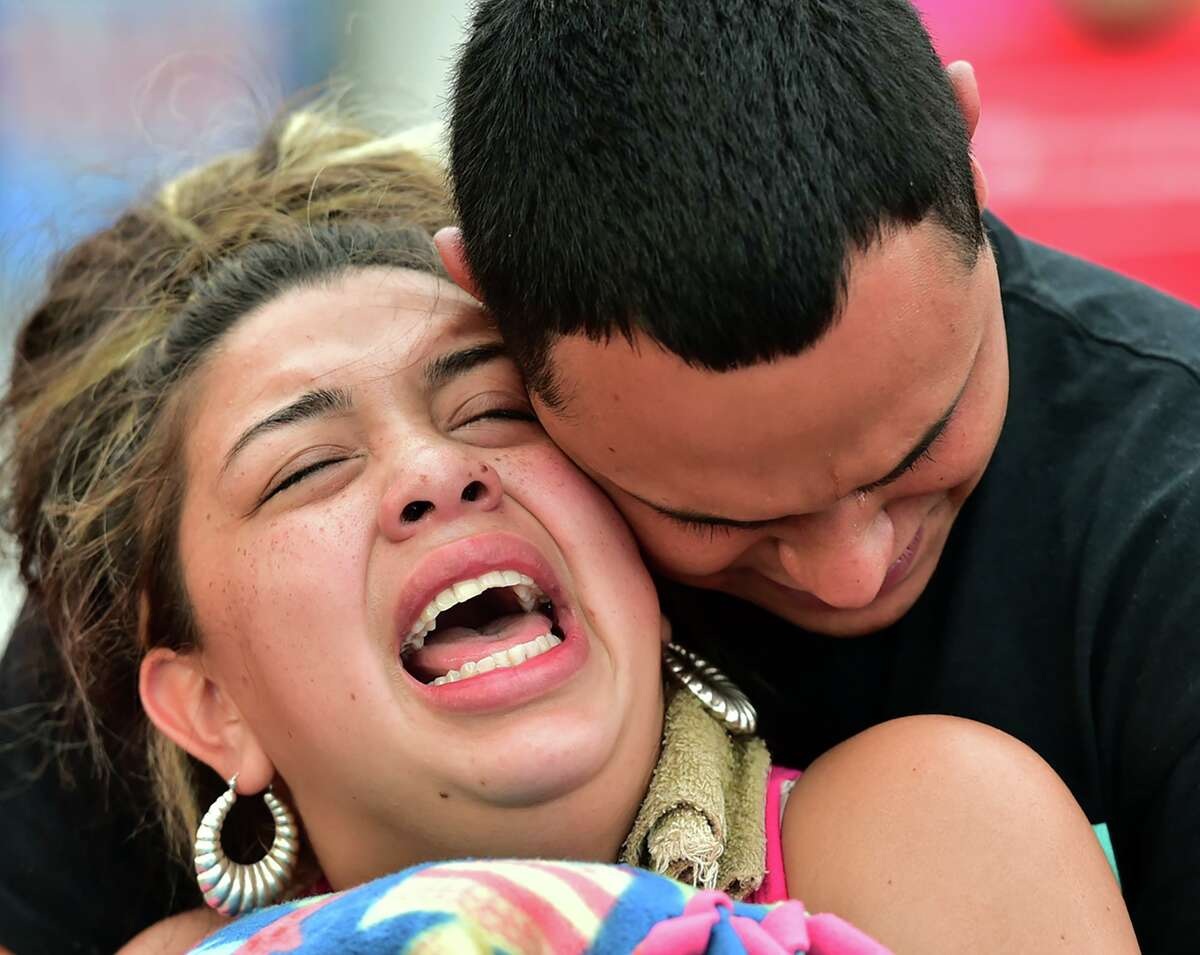 Kassandra Mendoza and Julio Garcia, parents of 6-year-old Saryah Perez, cry in anguish during a rally Monday.