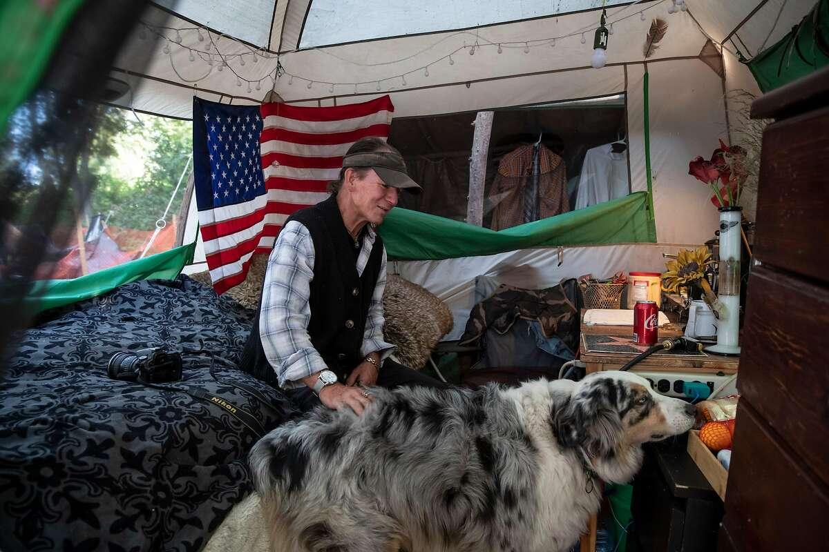 Mark Beckner and his dog, George, live inside a tent at the Friendship Garden homeless encampment at Harvey West Park in Santa Cruz.