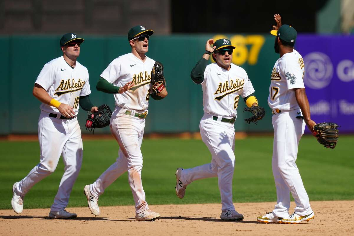 Seth Brown (15), Mark Canha (20) and Ramon Laureano (22) celebrate with Elvis Andrus (17) of the Oakland Athletics after beating the Tampa Bay Rays at RingCentral Coliseum on May 8, 2021.