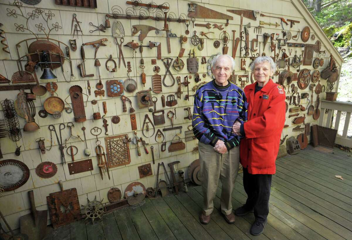Thelma and Myron Kandel pose in front of the wall of rusted metal objects collected over the years and displayed outside their home in Torrington, Conn., May 11, 2021.
