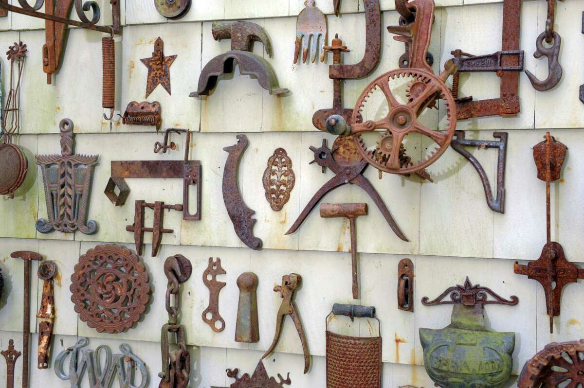 Thelma and Myron Kandel have collected hundreds of rusted metal objects that they display on a wall outside their home in Torrington, Conn., May 11, 2021.