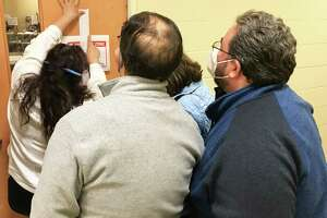 From left, forefront, Portland Selectman Ralph Zampano and Selectman James K. Tripp study the result being posted by Registrar of Voters Athena Neville, left. First Selectwoman Susan Bransfield is at the back (in blue).