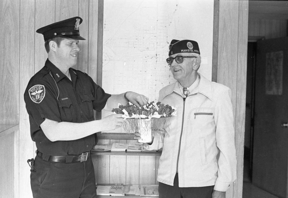 Manistee City Police officer Rick Taylor purchases a poppy this morning at Manistee City Hall from Martin Fredericksen, senior vice commander of Manistee's American Legion Post No. 10. The photo was published in the News Advocate on May 12, 1981. (Manistee County Historical Museum photo)