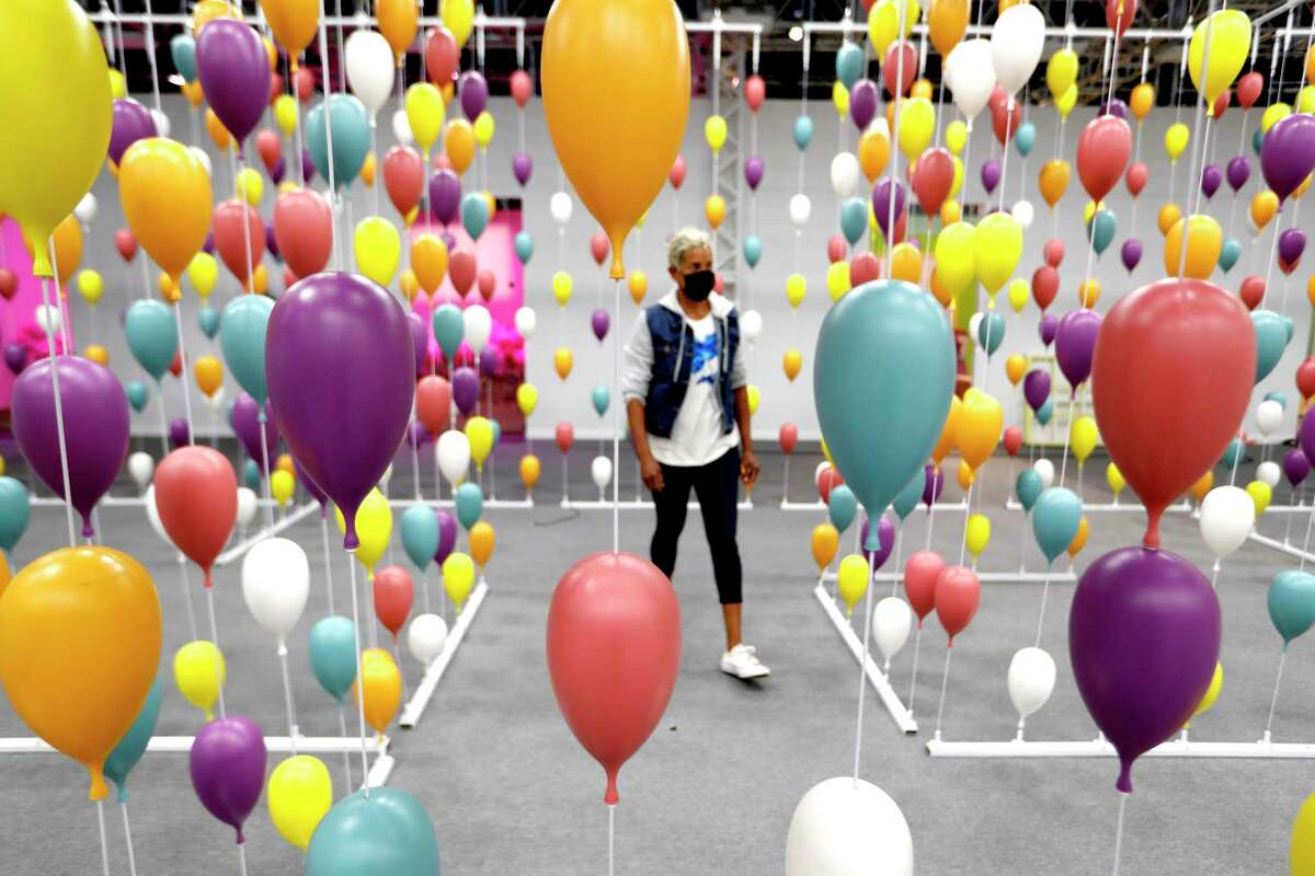 """Renee Froix, a producer, walks through balloons in the maze in the """"Oh, the Places You'll Go!"""" room inside the interactive The Dr. Seuss Experience - The Wondrous World of Dr Seuss at the George R. Brown Convention Center, Monday, May 10, 2021, in Houston."""