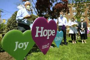 Manager of Pastoral Care Deacon Tim Bolton, left, leads the Garden of Hope Remembrance Ceremony during Nurses Week at St. Vincent's Medical Center in Bridgeport, Conn. on Tuesday, May 11, 2021. Bolton blessed a recently planted tree in honor of hospital nurses who have passed away in the last year.