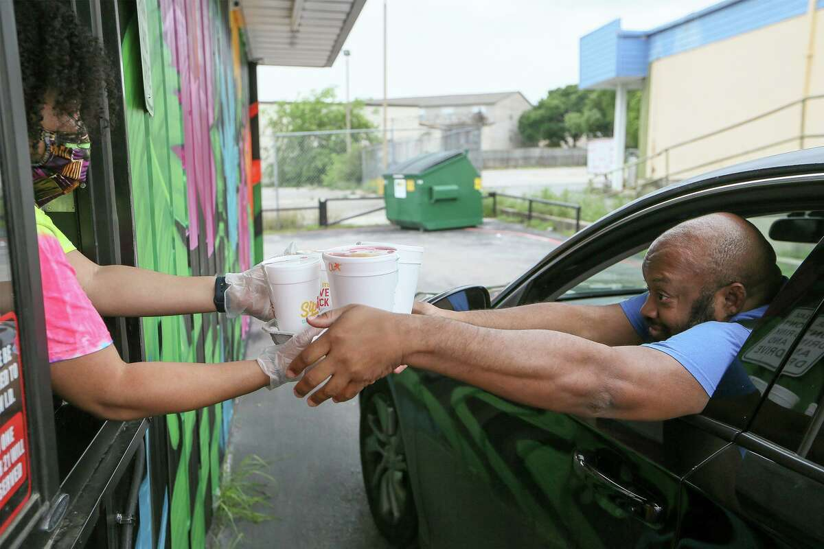 A man orders daiquiris from a drive-thru in Universal City. As Texas is close to making alcohol-to-go sales permanent, a task force is needed to help keep boozy drinks from teens.