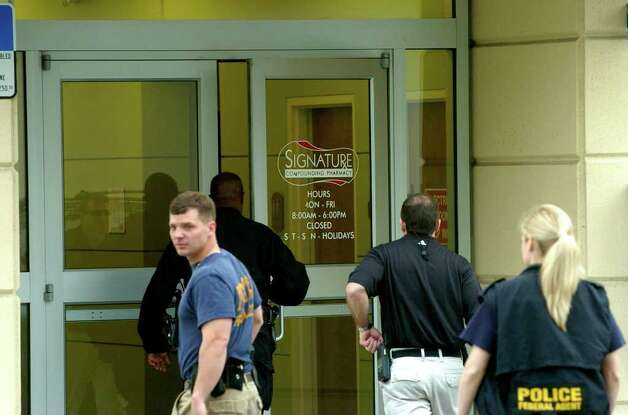 Law enforcement officials raid Signature Pharmacy in Orlando Feb. 27, 2007. The unusual case, spearheaded by Albany County's district attorney, takes New York narcotics agents and a federal task force deep inside a maze of shadowy pharmacies and web sites that have reaped millions of dollars in profit by allegedly exploiting federal and state prescription laws, according to court records. The Orlando business, Signature Compounding Pharmacy, did an estimated $36 million in business in 2006. (Paul Buckowski / Times Union) Photo: Paul Buckowski / Albany Times  Union