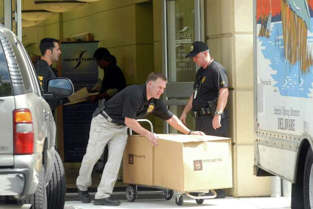 Law enforcement officials bring out boxes of items seized from the Signature Compounding Pharmacy in Orlando, Feb. 27, 2007. (Paul Buckowski / Times Union) Photo: Paul Buckowski / Albany Times Union