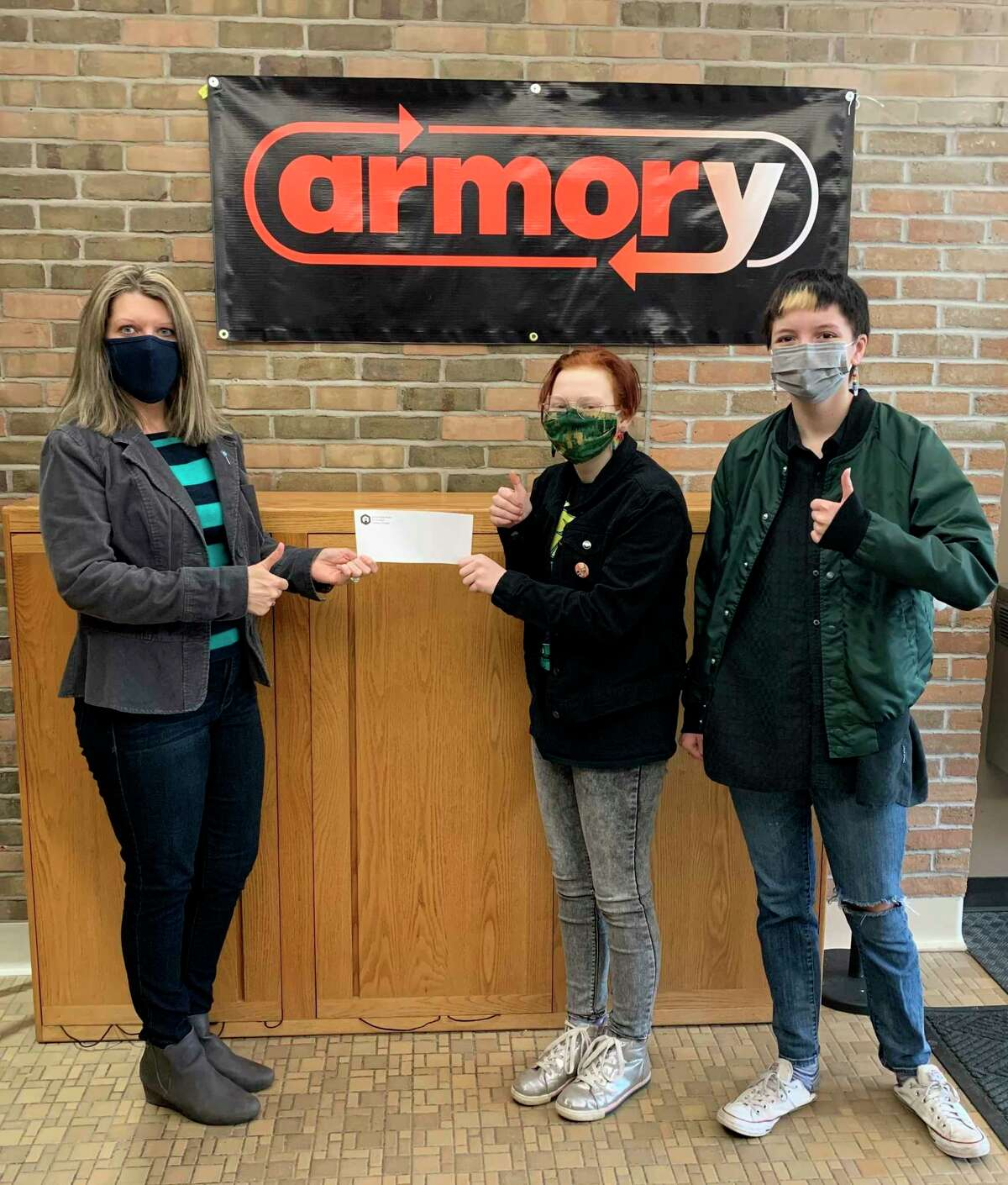 Traci Smith (left),Manistee County Child Advocacy Center family advocate, receives a donation fromArmory Youth Project JuniorAchievement students Eren Hawkins and Sylis Patterson. (Courtesy photo)