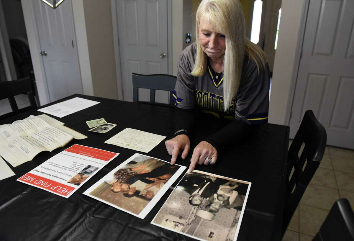 Cindy Dort looks at hold photographs for her birth mother, Bonnie Jeanne Hutton, on Tuesday, May 4, 2021, at her home in Milton, N.Y. Cindy, who was adopted, is searching for her birth family. (Will Waldron/Times Union)