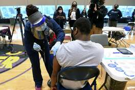 Gary Moore Jr., 16, receives his first dose of the Pfizer COVID-19 vaccine from New Haven City Health Department LPN Stephanie Rice at a COVID-19 vaccine clinic for people 16 and older at Hill Regional Career High School in New Haven on April 15, 2021.