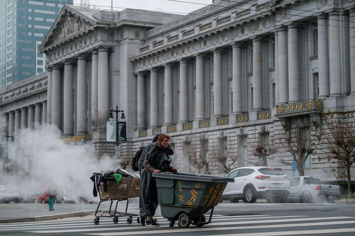 Homeless people push their belongings near City Hall in San Francisco. Gov. Gavin Newsom is proposing to spend some $12 billion on homeless housing and services.