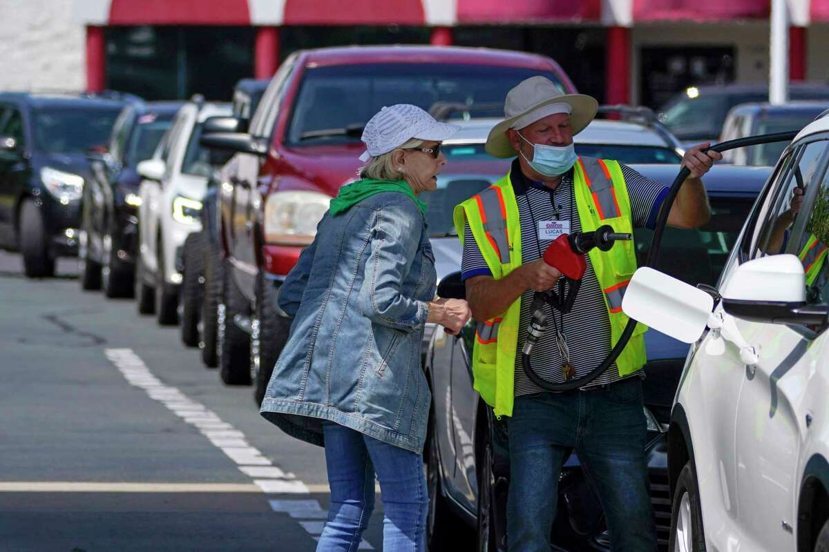 A customer helps pumping gas at Costco, as other wait in line, on Tuesday, May 11, 2021, in Charlotte, N.C. Colonial Pipeline, which delivers about 45% of the fuel consumed on the East Coast, halted operations last week after revealing a cyberattack that it said had affected some of its systems.