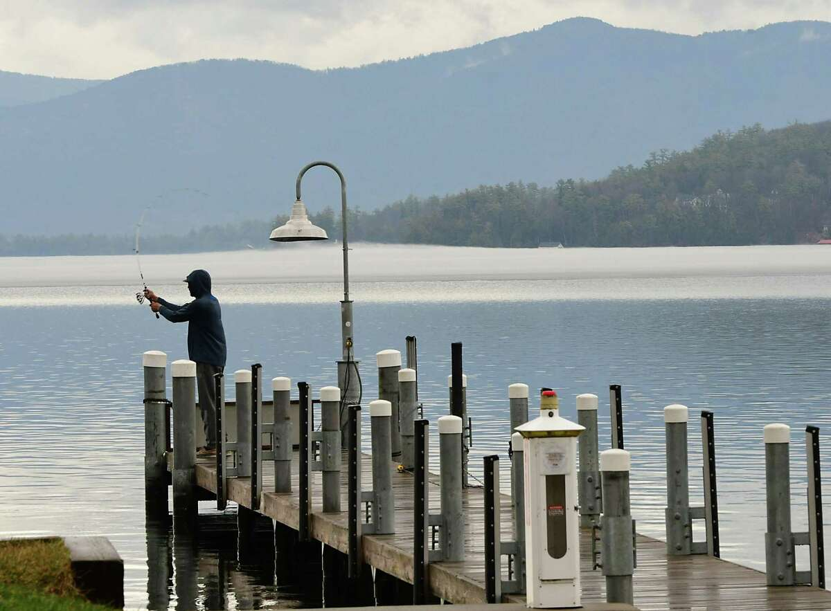 A fisherman casts his line as he fishes in a light rain from a pier on Friday, March 26, 2021 in Lake George, N.Y. (Lori Van Buren/Times Union)
