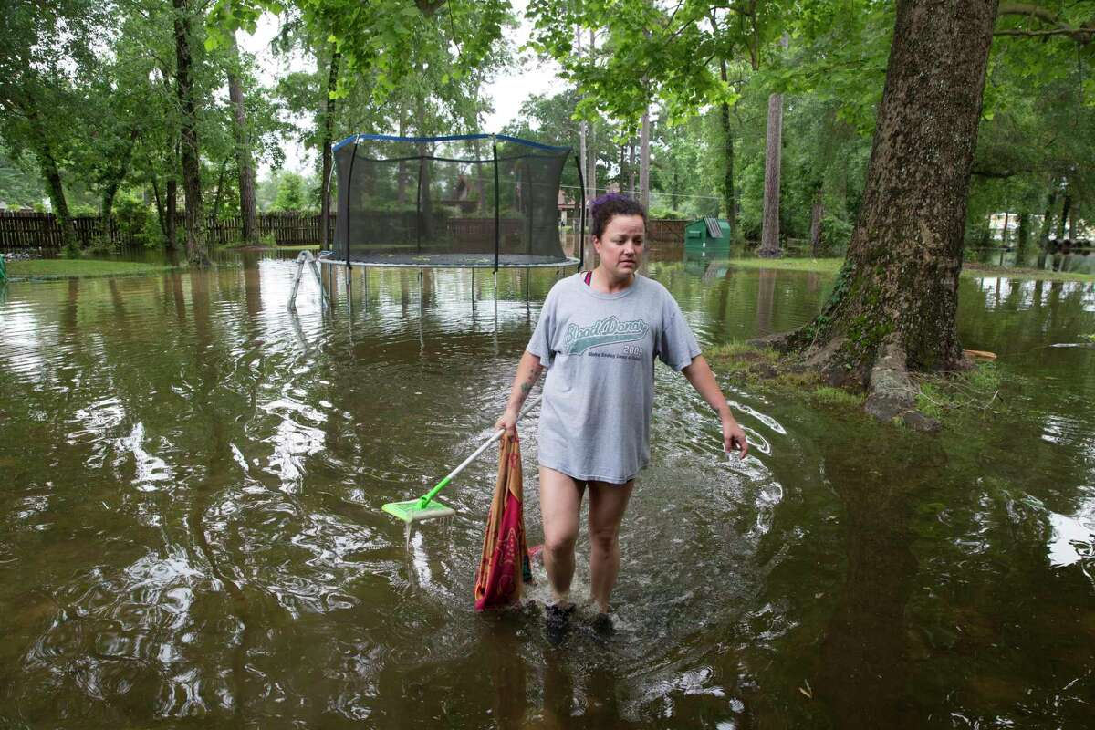 Jennifer Wilson walks in her flooded yard to retrieve floated items on Wednesday, May 8, 2019, in Porter. The Wilson family received about a foot of flood water in the house from the Tuesday rain. Wilson and his wife, Jennifer, has experienced three hurricane floods, including Harvey, in the past but none of them had more water in the house than Tuesday's rain. The family lived four months without carpet after Harvey flood and they finally started to feel stable about nine months ago.