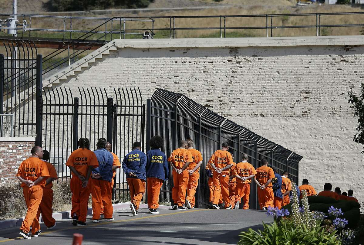In this Aug. 16, 2016, file photo, a row of general population inmates walk in a line at San Quentin State Prison in San Quentin, Calif. California is giving 76,000 inmates the opportunity to leave prison earlier.