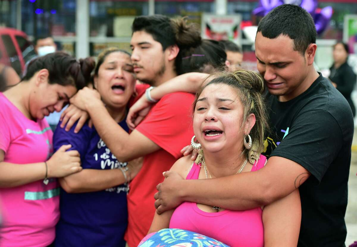 Kassandra Mendoza and Julio Garcia, parents of Saryah Perez and other family members cry during a rally Monday evening to honor their 6 year-old who was shot and killed Sunday night.