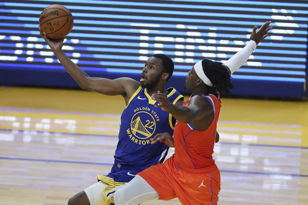Golden State Warriors' Andrew Wiggins, left, shoots against Oklahoma City Thunder's Luguentz Dort during the first half of an NBA basketball game in San Francisco, Saturday, May 8, 2021. (AP Photo/Jed Jacobsohn)