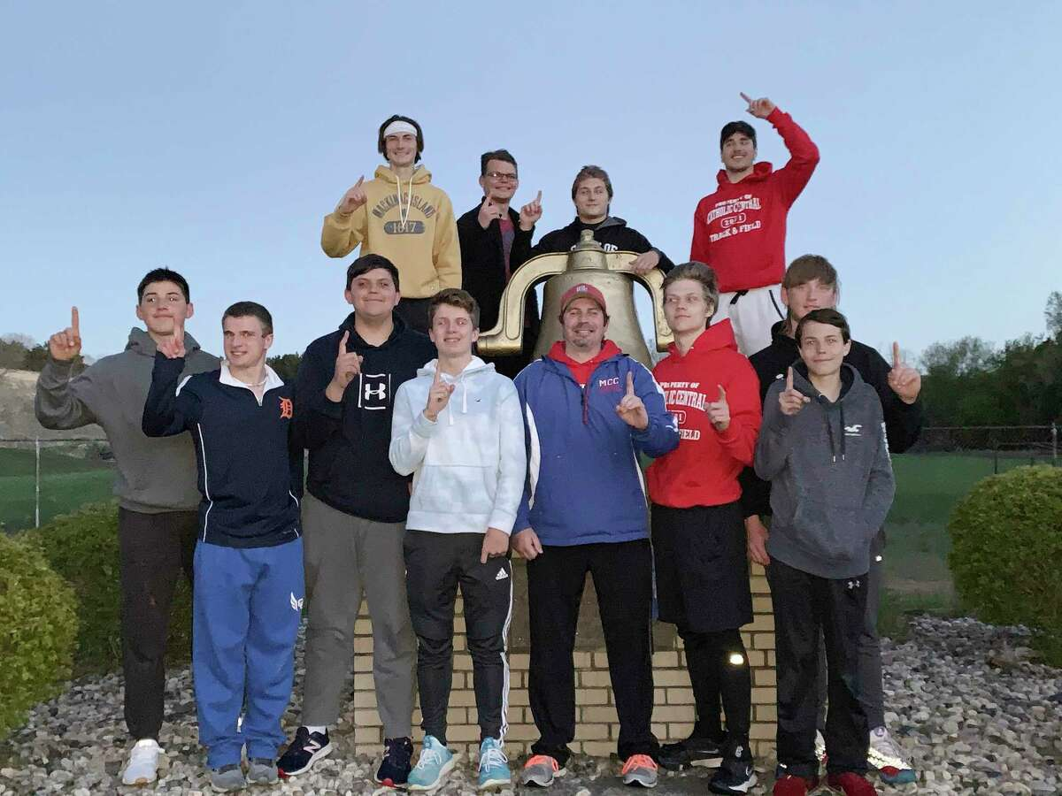 The Manistee Catholic Central boys track and field team pose by their victory bell after winning the West Michigan D League championship in Marion on Tuesday. (Courtesy photo)