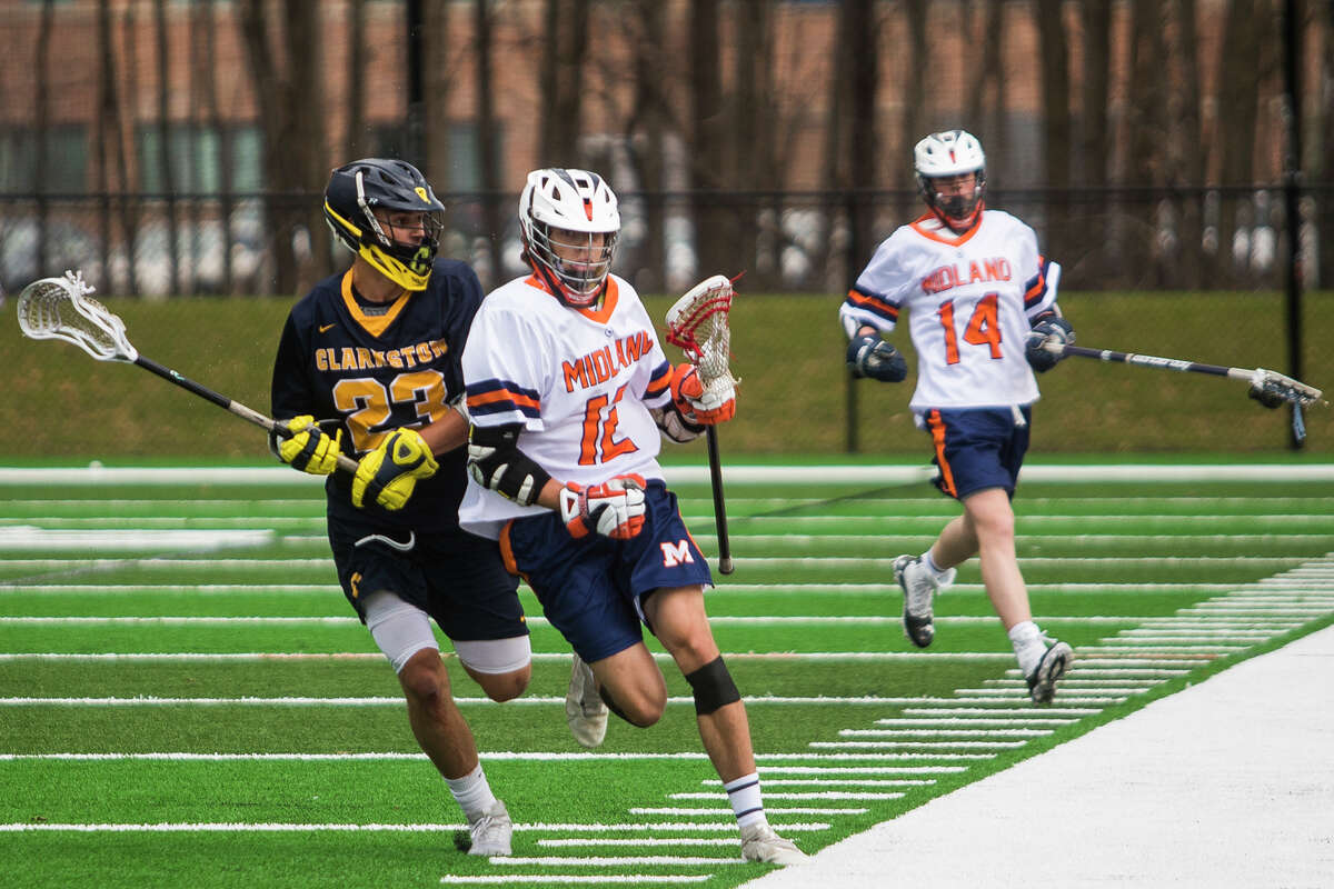 Midland-Dow's Tucker Pomranky (middle) advances the ball upfield during an April 9, 2021 game against Clarkston at Dow High. Midland-Dow clinched its sixth Saginaw Valley League championship in the past seven years on Tuesday.