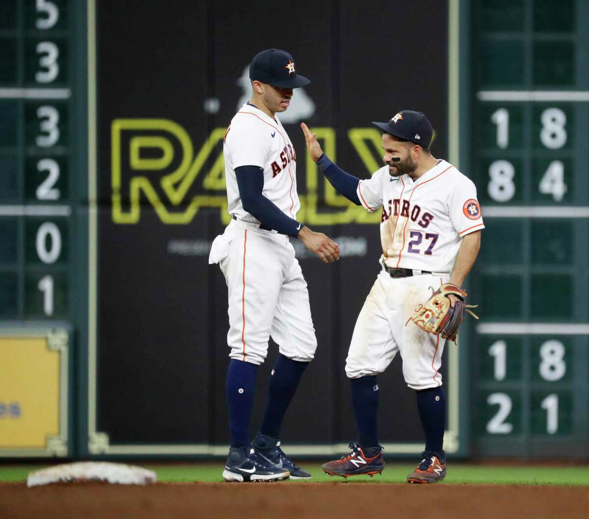 Houston Astros shortstop Carlos Correa (1) and second baseman Jose Altuve (27) celebrate the Astros 5-1 win over the Los Angeles Angels dafter an MLB baseball game at Minute Maid Park, Tuesday, May 11, 2021, in Houston.
