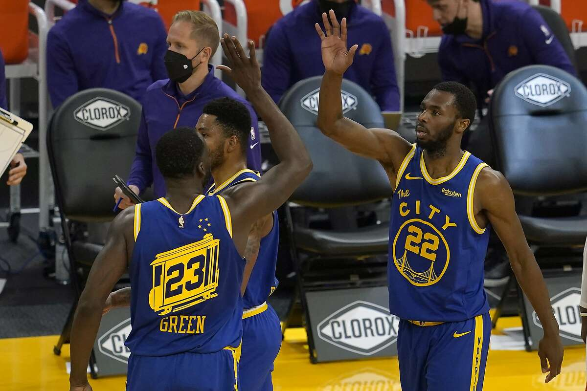 Golden State Warriors forward Andrew Wiggins (22) celebrates with forward Draymond Green (23) during the first half of an NBA basketball game against the Phoenix Suns in San Francisco, Tuesday, May 11, 2021. (AP Photo/Jeff Chiu)