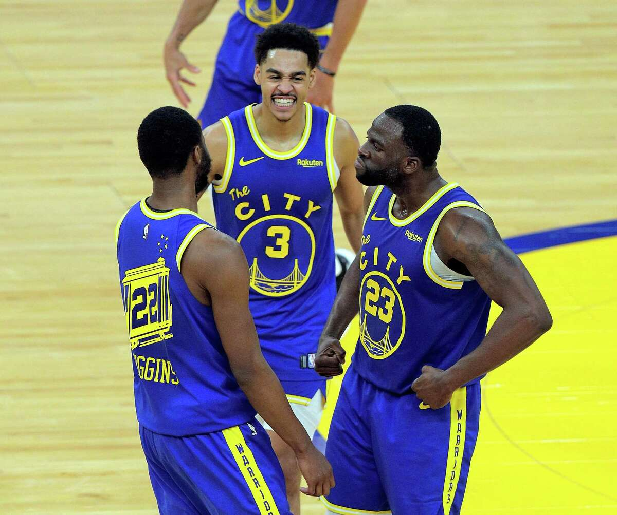 Draymond Green (23) celebrates with Andrew Wiggins (22) and Jordan Poole (3) late in the second half as the Golden State Warriors defeated the Phoenix Suns 122-116 at Chase Center in San Francisco, Calif., on Tuesday, May 11, 2021.
