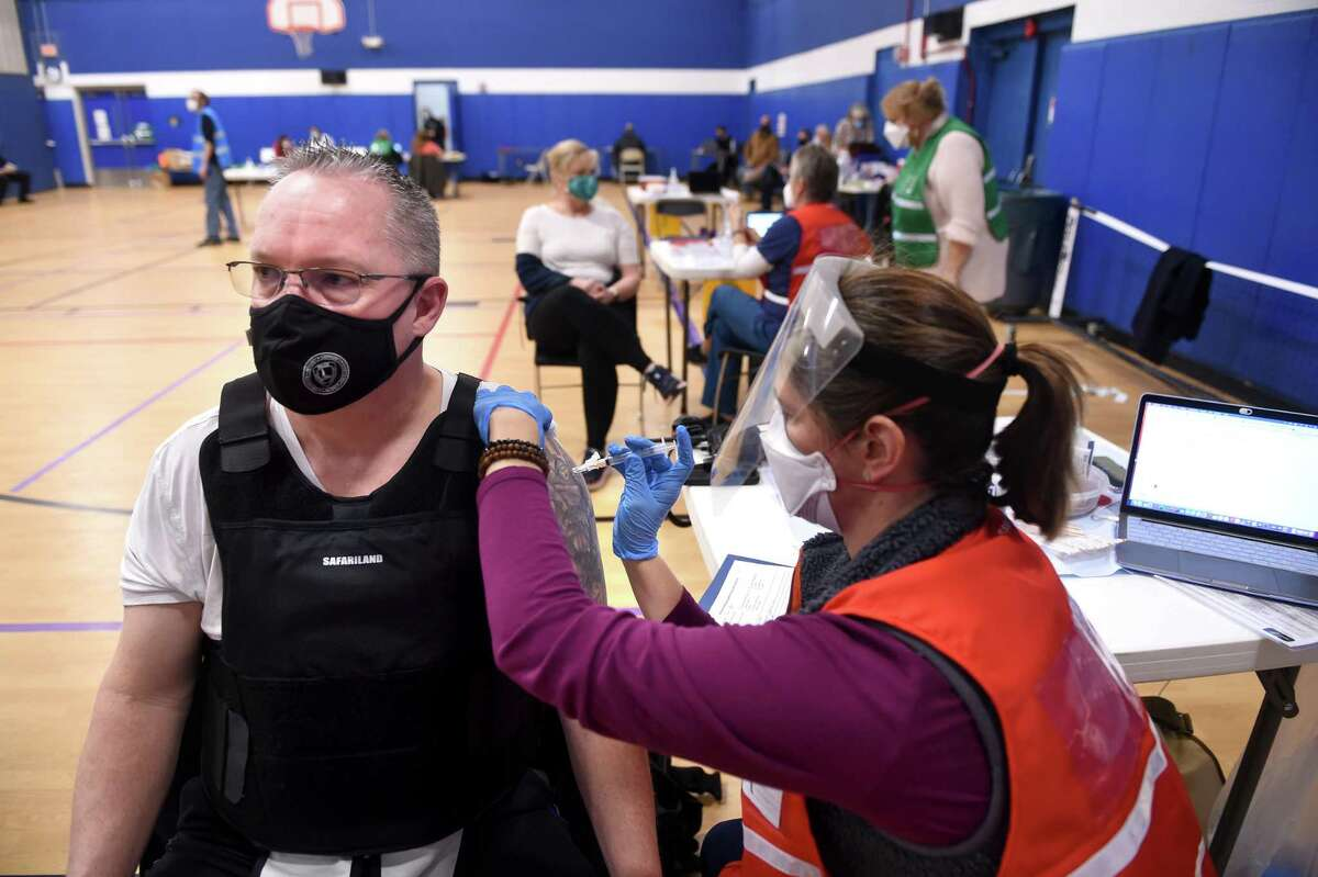 East Haven Police Sgt. Joseph Mulhern (left) gets a dose of the Moderna COVID-19 vaccine by RN Jennifer VanderWyk at the Madison Town Campus gymnasium on Jan. 6, 2021.