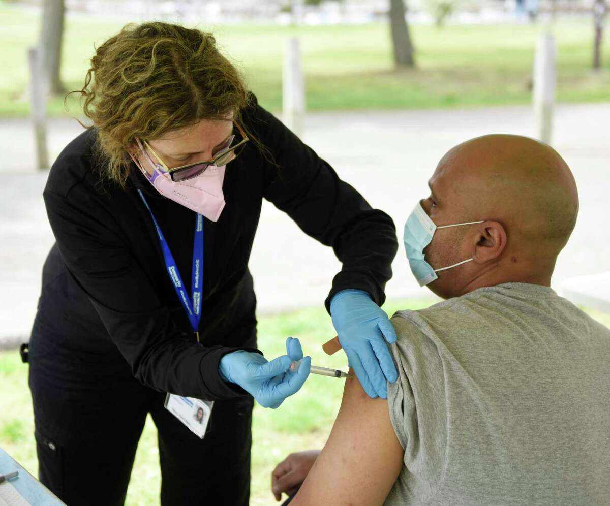 Stamford's Jose Virella gets vaccinated by Mary Ann Llinas at the Community Health Centers walk-in COVID-19 vaccination clinic at Cove Island Park in Stamford, Conn. Sunday, May 2, 2021. CCH provided patients with the single-dose Johnson & Johnson vaccine Sunday with no appointment necessary.