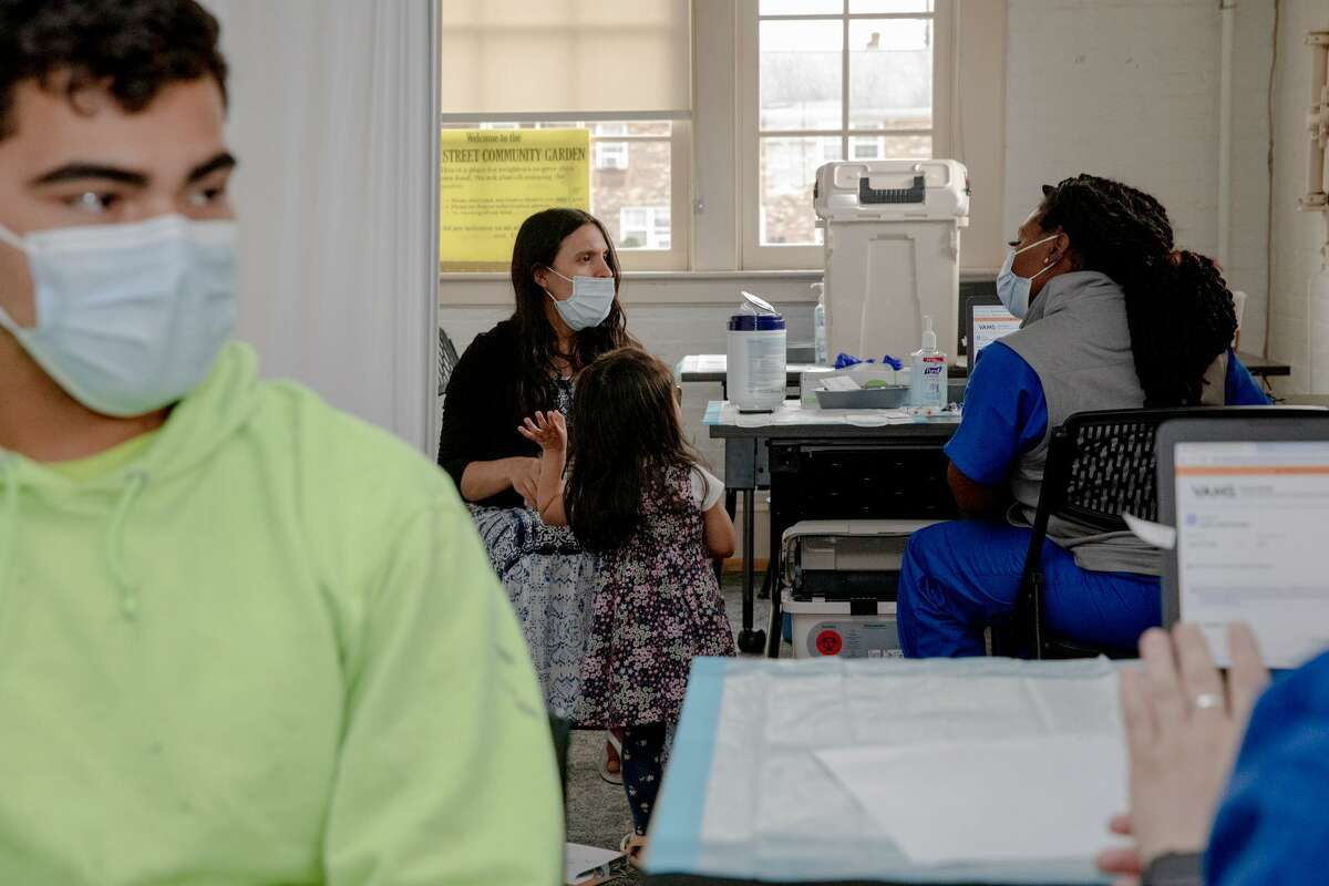 Mirsa Montufar, second from left, listens to the medical personnel, Stephanie Brown, before receiving her vaccine at the Griffin mobile clinic in Manchester. Her husband, Jose Valenzuela, left, said that he didn't plan to get vaccinated at first, but his church convinced him to come to the walk-in vaccination site with his wife.