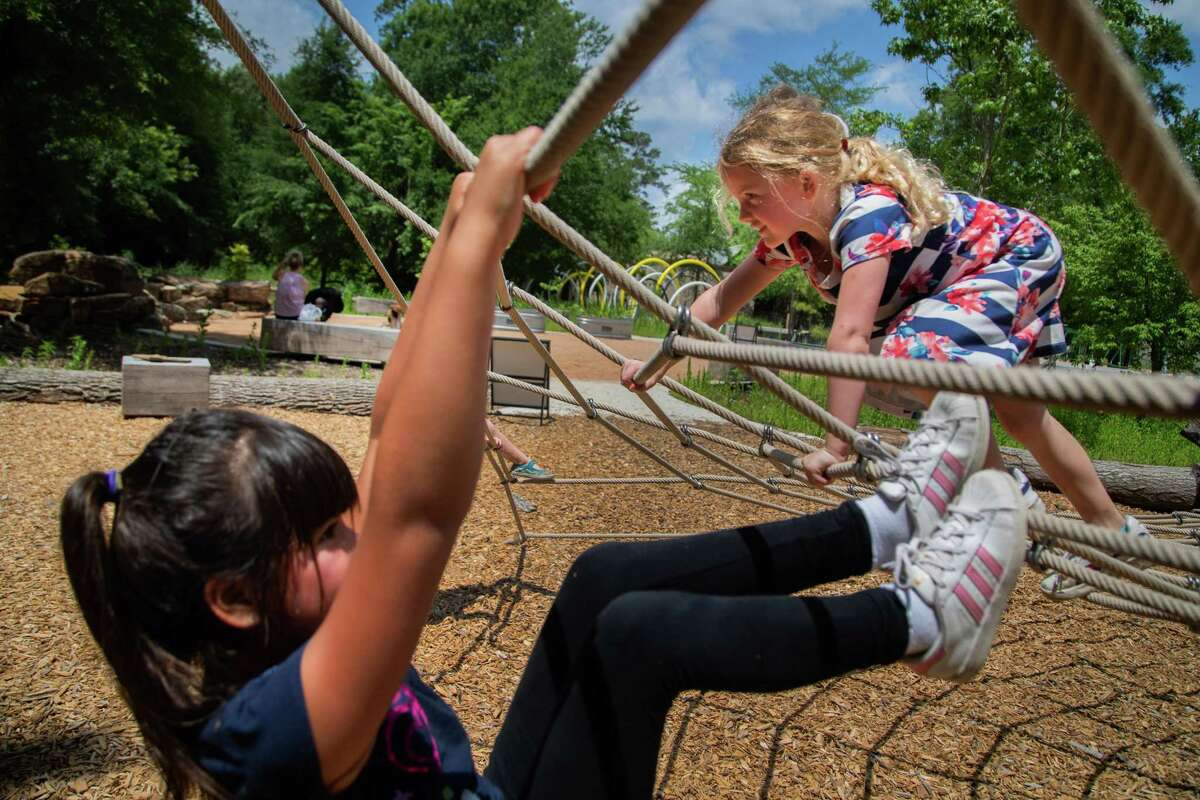 Shanti Del Rio, left, 7, and Eloise Rotolo, 7, play on a spider web together at the Houston Arboretum & Nature Center's new and much-anticipated Nature Playscape, Monday, May 10, 2021, in Houston.