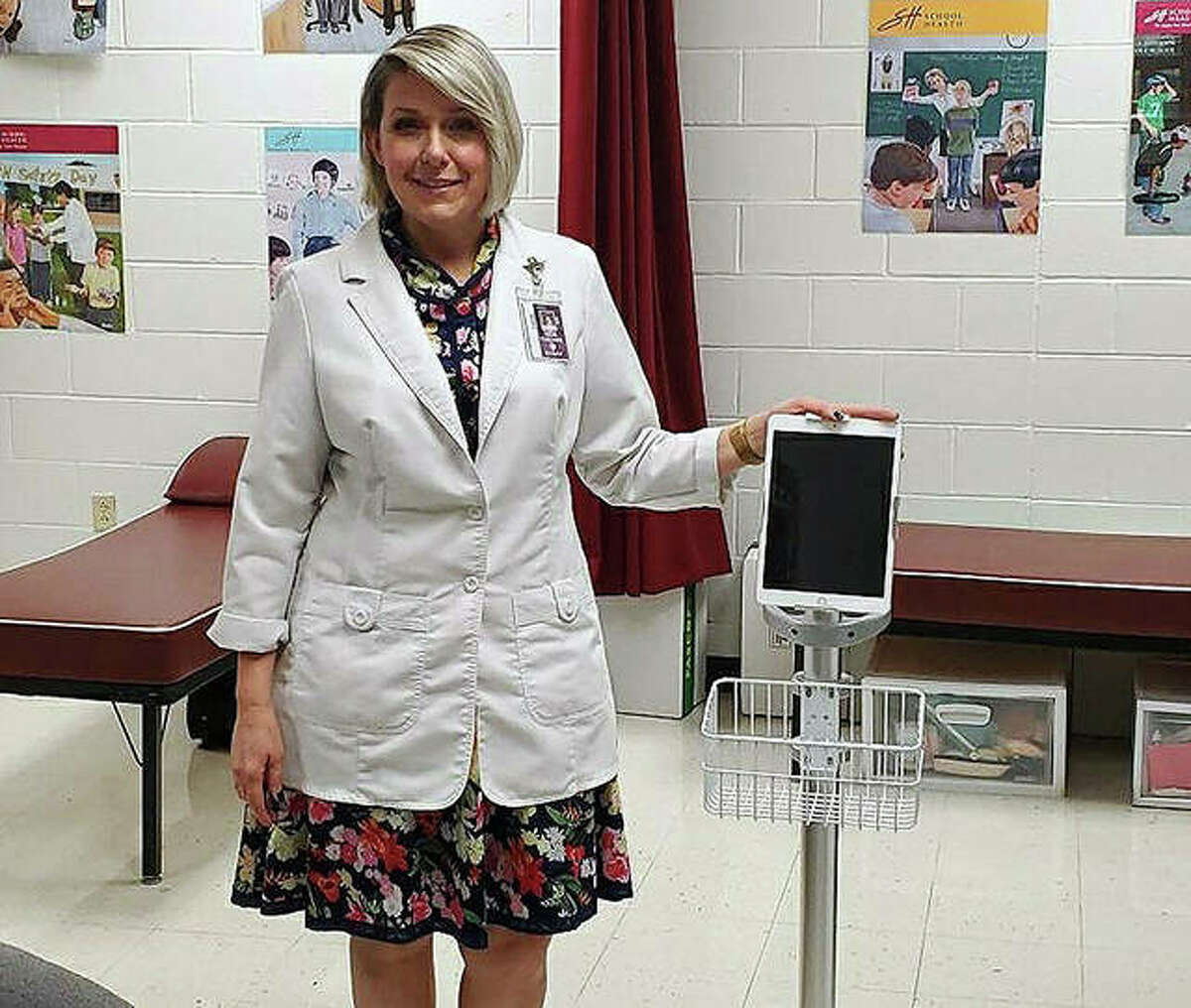 Collinsville Middle School Nurse, Debra Welch, poses with the tablet computer that Hazel Health provided her to use for student telehealth consultations.