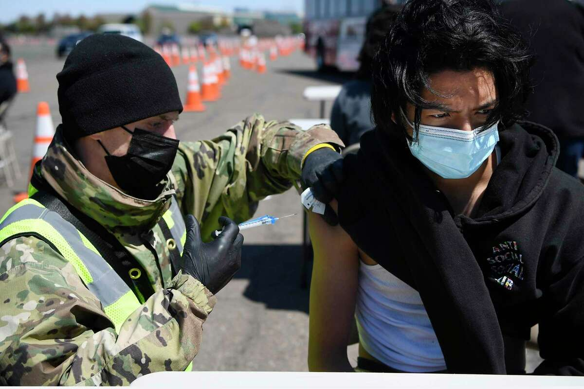 Connecticut National Guard medic Todd Smith, left, administers a shot to East Hartford High School senior Alberto Salazar Rodriguez at a mass vaccination site at Pratt & Whitney Runway in East Hartford, Conn., Monday, April 26, 2021.