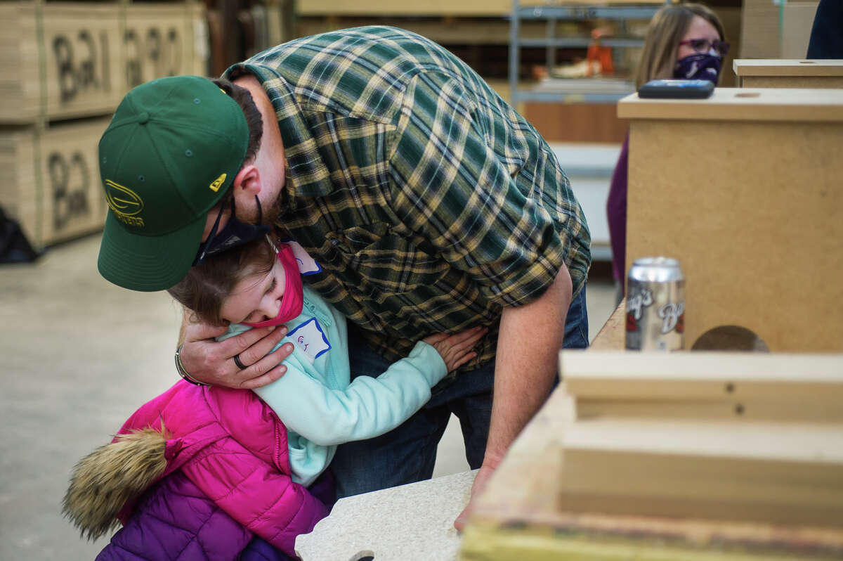 Finley Braendle, 6, hugs her dad, Jon Braendle, after building a step stool together during a father and daughter event hosted by Self Love Beauty and sponsored by Three Rivers Corporation, Modern Realty, and Hemlock Semiconductor Tuesday, May 11, 2021 at Three Rivers Corporation. The pairs enjoyed a pizza dinner before working together on a STEM-based building activity and taking part in other confidence-focused activities. (Katy Kildee/kkildee@mdn.net)