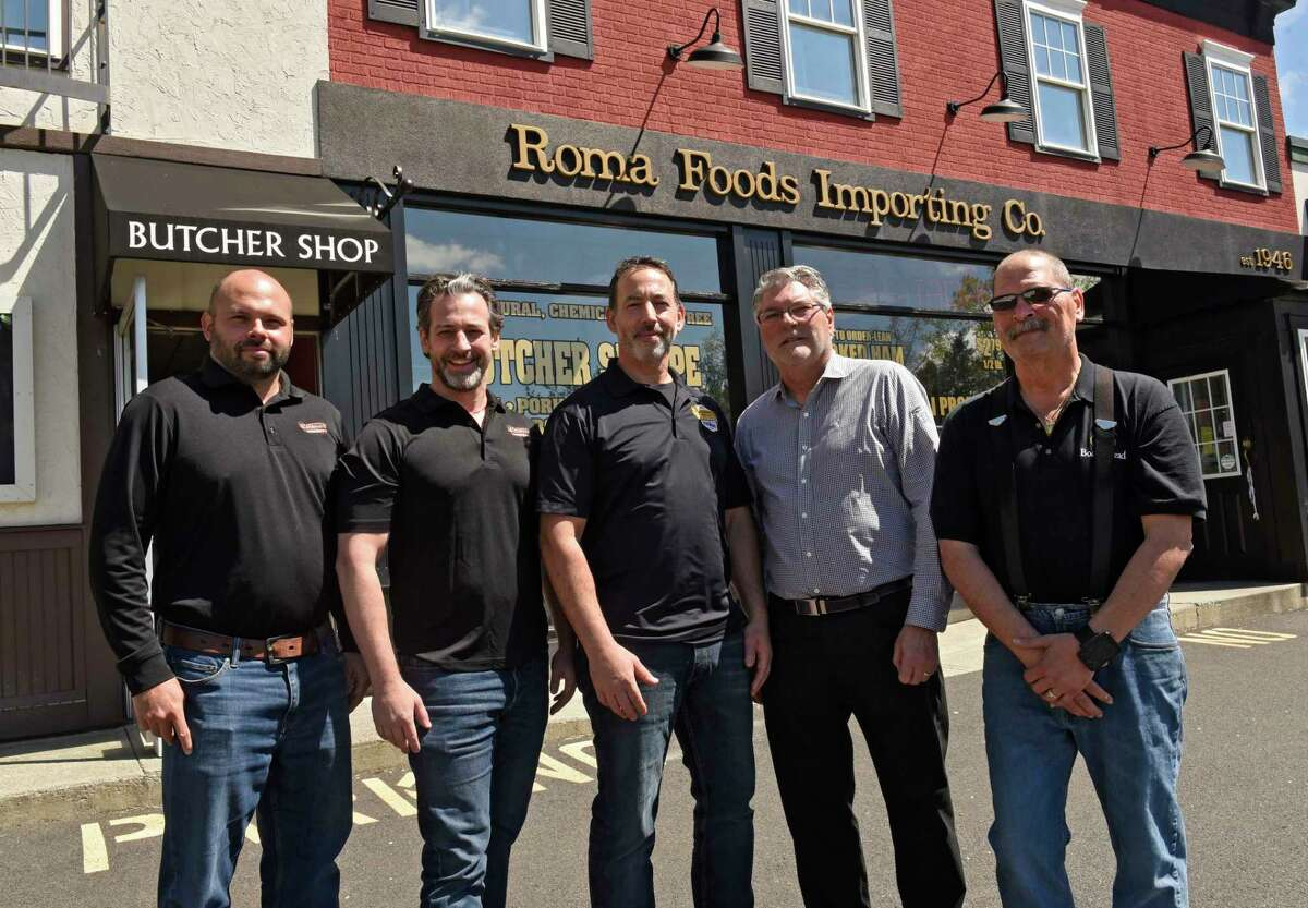 From left, Thomas (T.J) Conti, and brothers August Cardona and Robert Cardona Jr. stand with Roma owners Frank Bolognino and his brother Peter Bolognino in front of Roma Foods Importing Co. on Wednesday, May 12, 2021 in Latham, N.Y. The Cardona brothers and Conti recently bought both locations of Roma Foods Importing Co., in Latham and Saratoga Springs. (Lori Van Buren/Times Union)