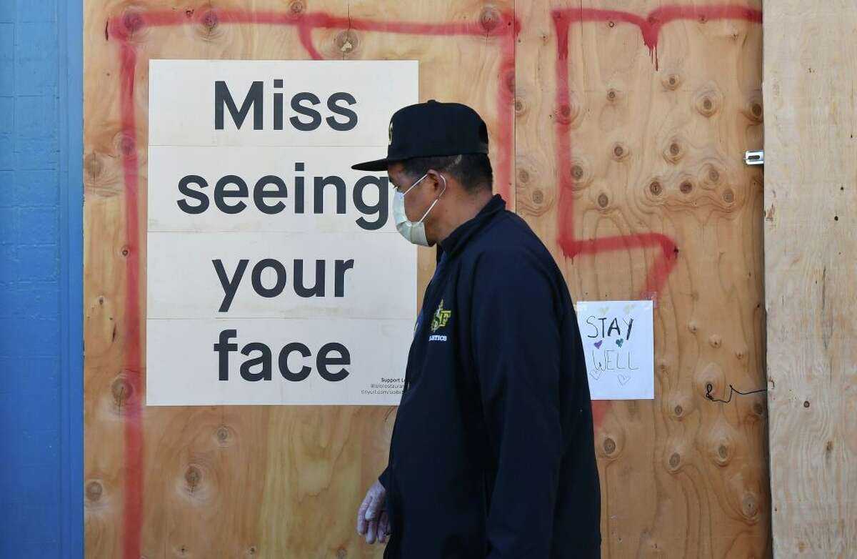 A man in a face mask walks by a sign posted on a boarded up restaurant in San Francisco on April 1, 2020.