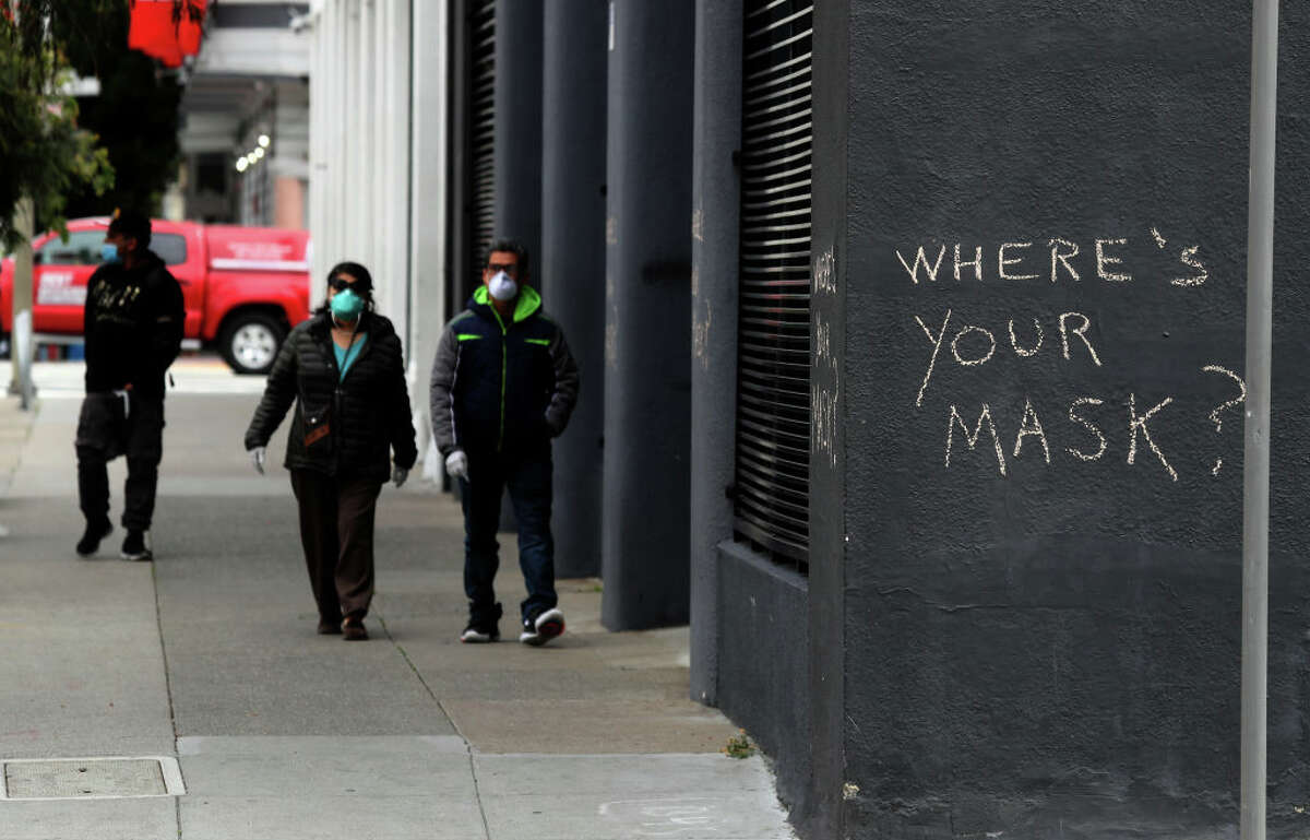 Pedestrians walk by graffiti encouraging the wearing of masks on April 20, 2020 in San Francisco, California.