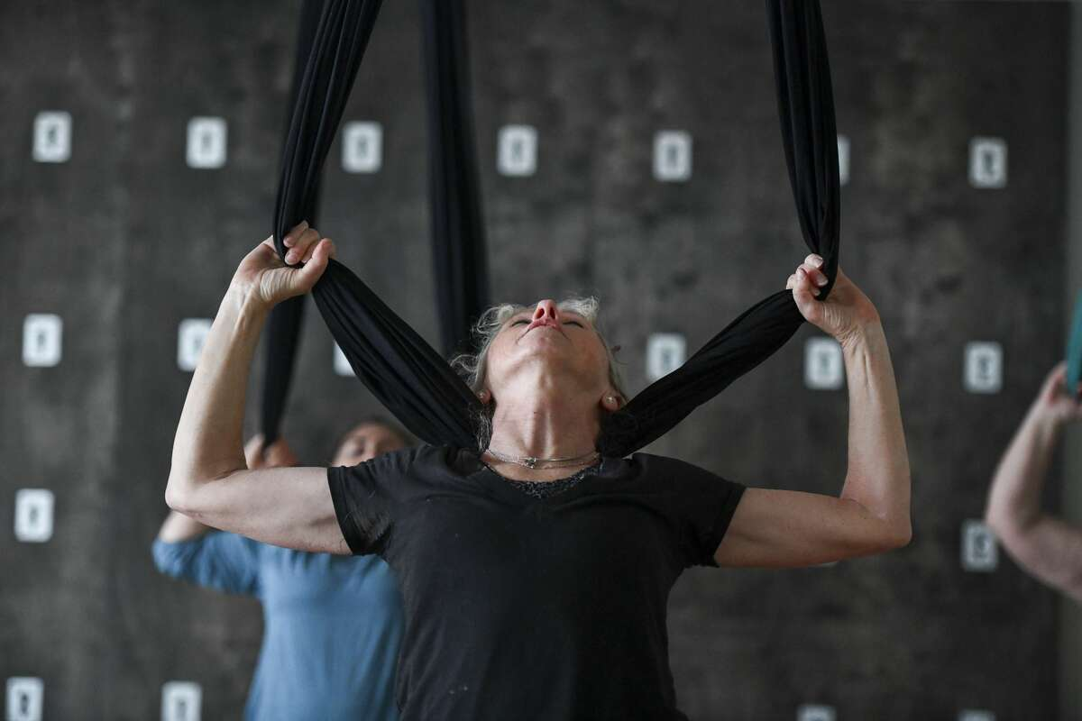 Cyndi Simpson uses the hammock to rest her head during an aerial yoga class Jan. 10 at Midland Yoga Works.
