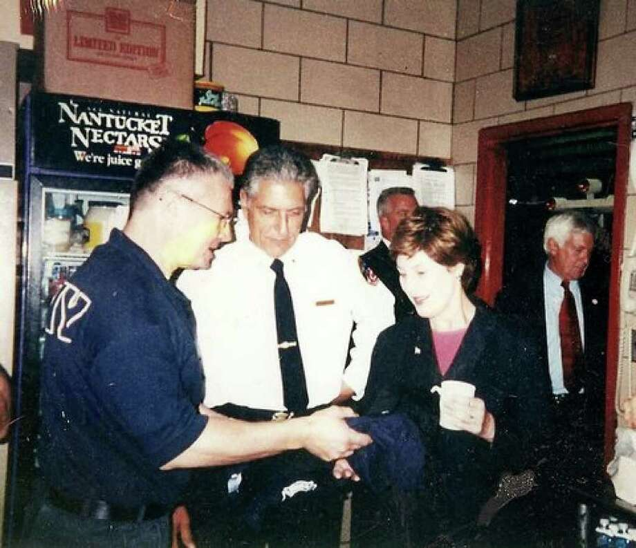 Firefighter Glenn Foulkes, left, hands Laura Bush an Engine 54 T-shirt shortly after 9/11 at the Engine Company 54 firehouse in Manhattan. (Courtesy Mary Beth Buchner)