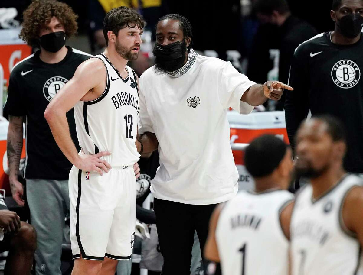 Brooklyn Nets forward Joe Harris, left, confers with injured guard James Harden during a timeout in the first half of the team's NBA basketball game against the Denver Nuggets on Saturday, May 8, 2021, in Denver.