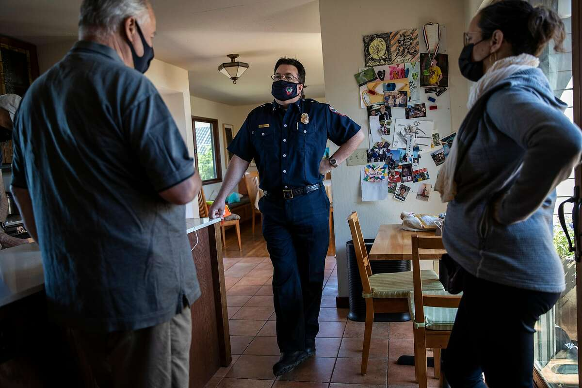 Contra Costa County Fire Protection District Fire Chief Lewis Broschard, center, talks with Wildcat Watch volunteers James Mahshi, left, and Maya Churi, in Kensington, Calif., Tuesday, May 11, 2021.