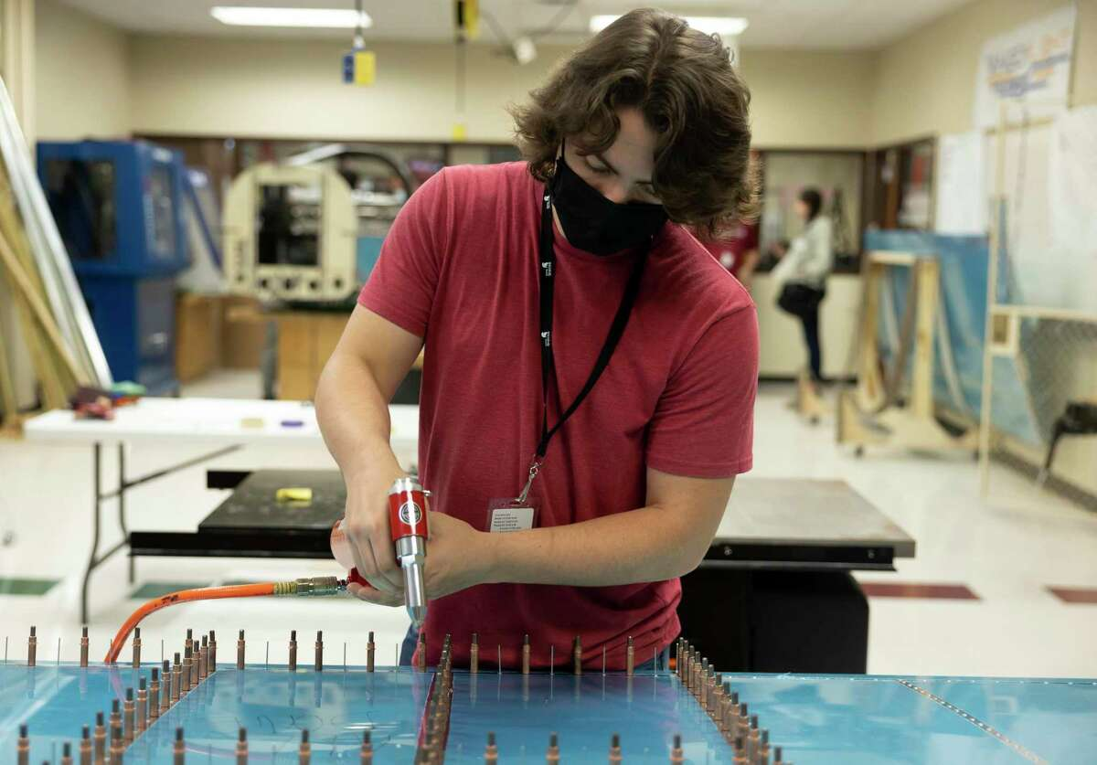 Kaleb Bowers, senior, places nails on a wing of a plane during a CTE practicum course in aerospace engineering at Porter High School, Tuesday, May 12, 2021, in Porter. The class expects the aircraft to be finished by Spring 2022 and have hopes to fly it out of the Conroe airport.